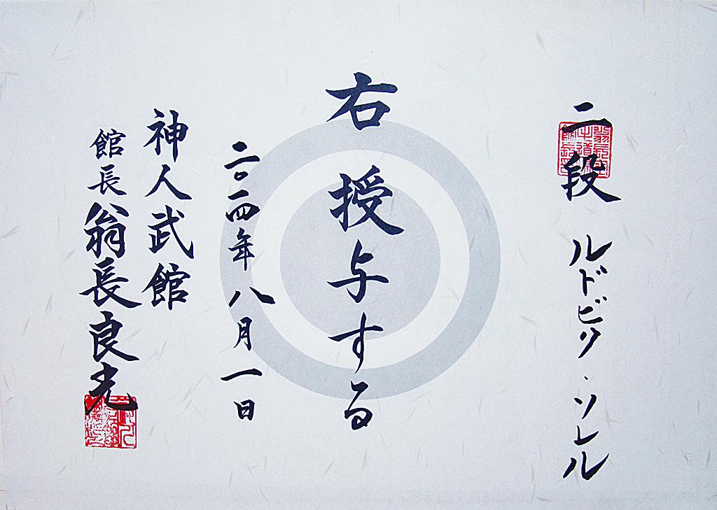 <em>La personne mentionnée à droite se voit attribuer le rang indiqué. Donné le 1er août 2014.<br> Shinjinbukan. Kanchō, Onaga Yoshimitsu</em><br> <strong>Ni Dan, Ludovic SOLER</strong>